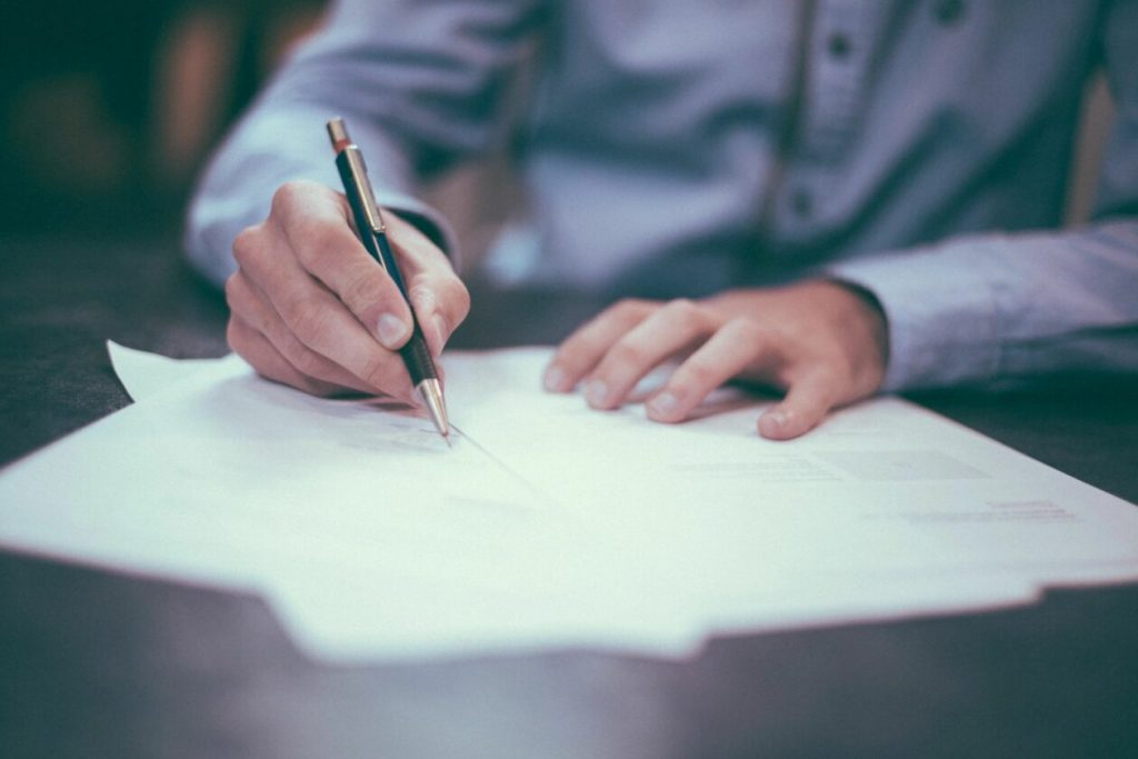 man signing business papers